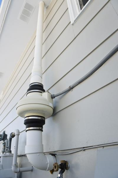 A radon mitigation fan installed on the side of a house.