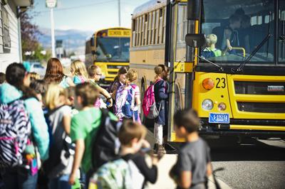 Students file onto a school bus
