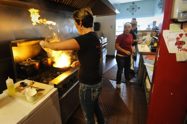 Mariela Petroski, owner of Cielo Cocina, flambes shrimp for an order of shrimp tacos in this IR file photo.