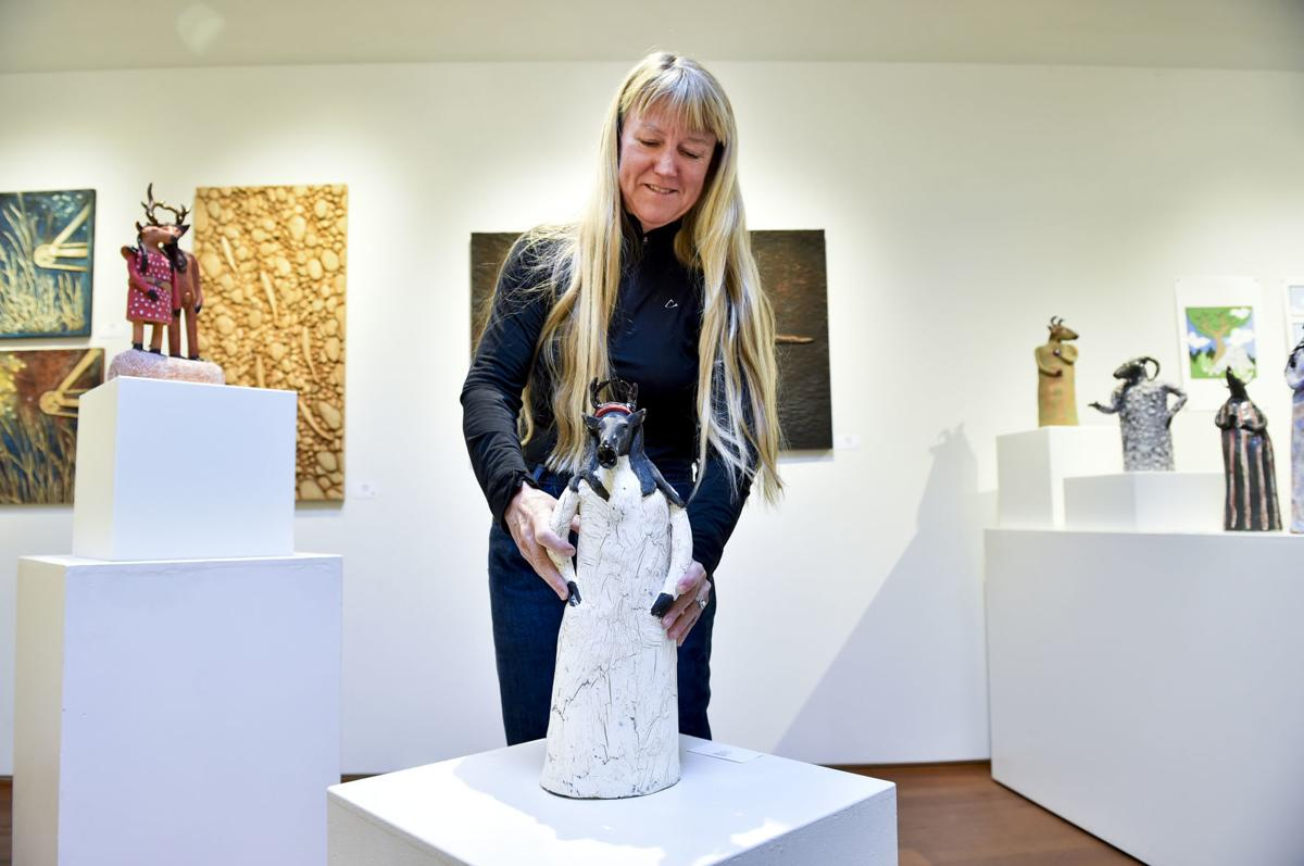Betsey Hurd positions one of her works at 1+1=1 Gallery