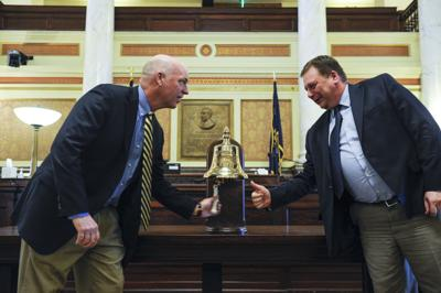 Gov. Greg Gianforte, left, and Senate President Sen. Mark Basdel, ring the replica USS Montana
