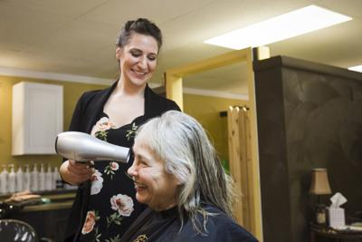 Mallory Jacobson cuts the hair of a God's Love resident