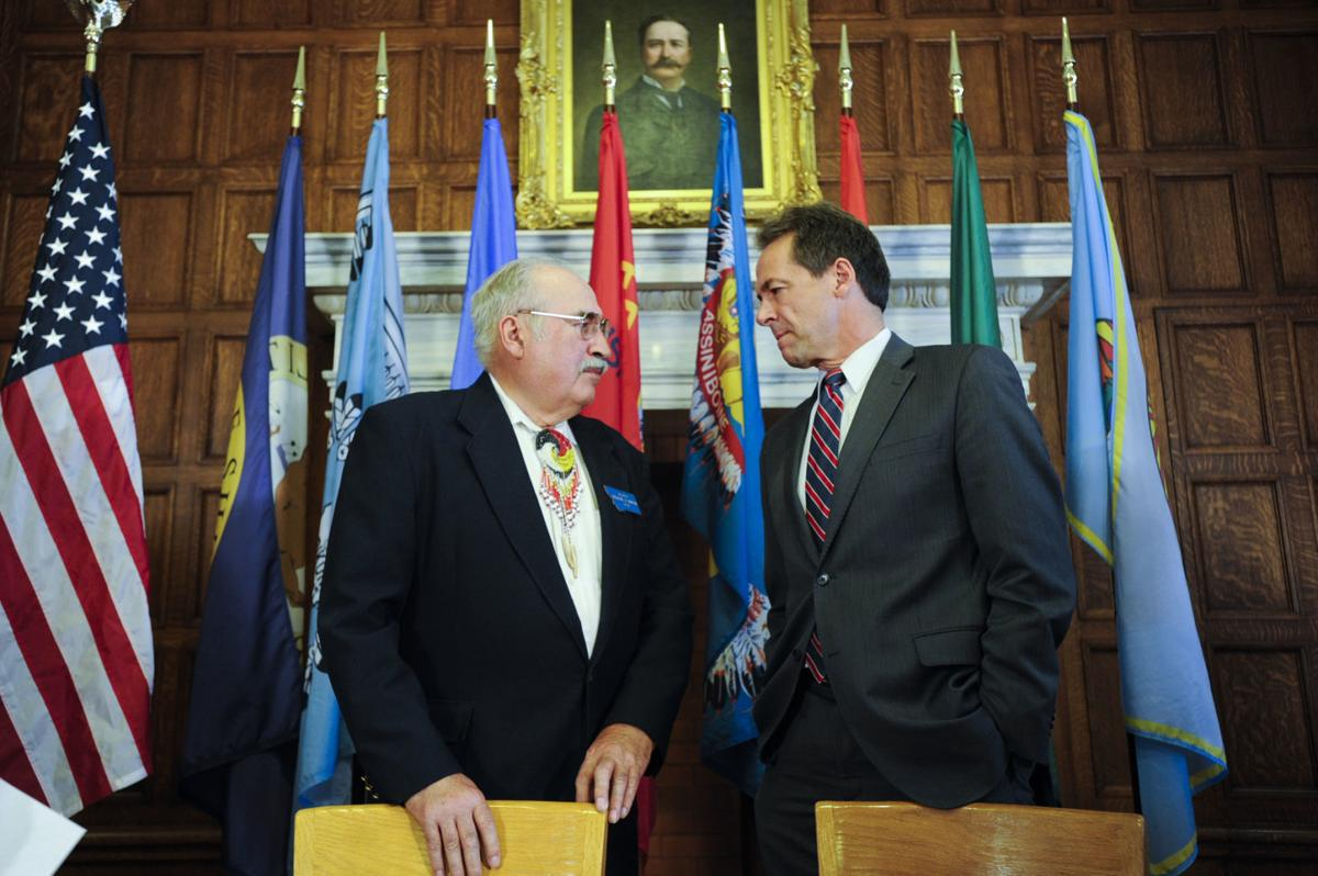 Gov. Steve Bullock, right, talks with Sen. Frank Smith