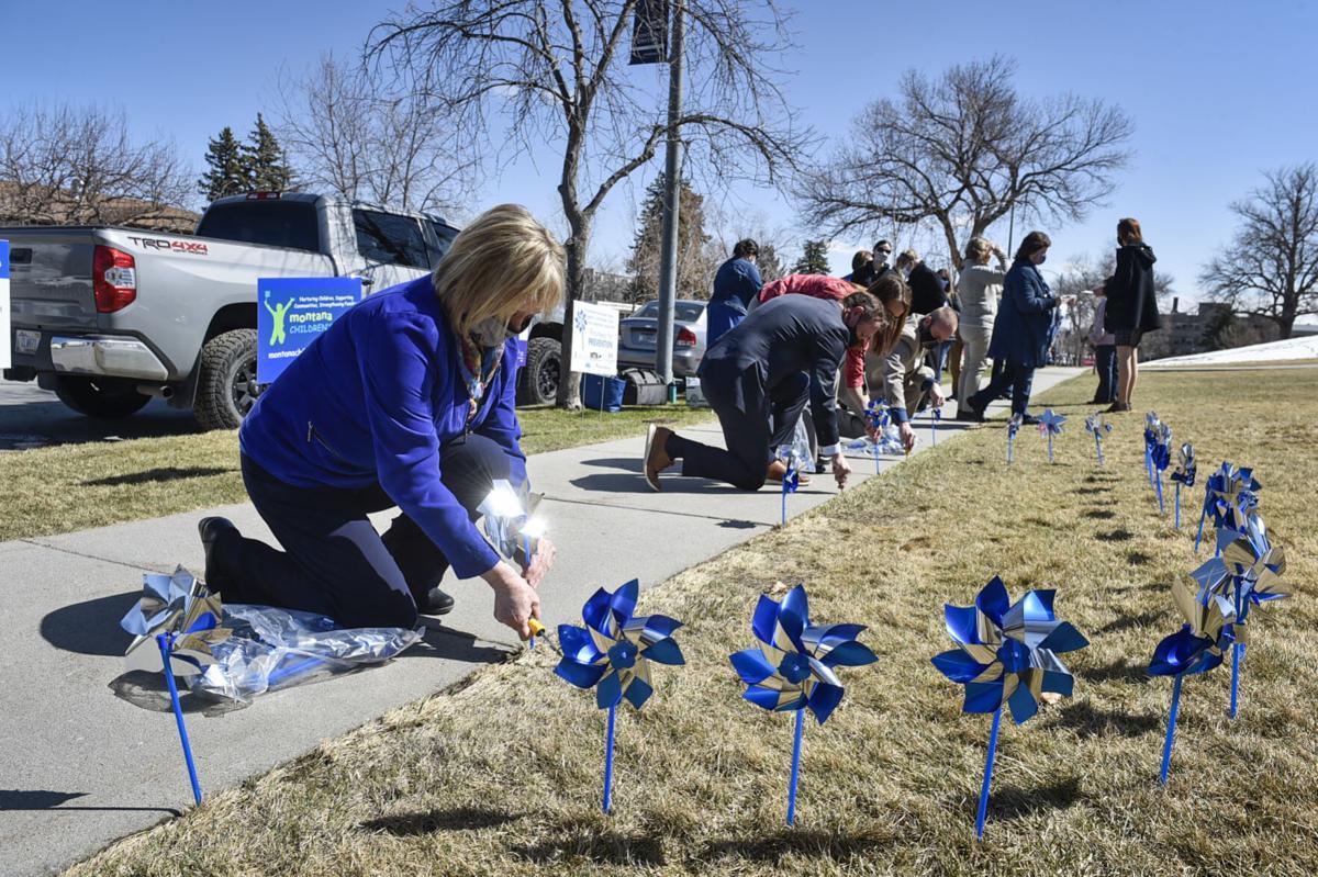 Lt. Gov. Kristen Juras, left, places a pinwheel in the ground