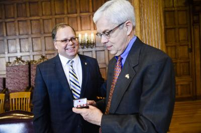 Canadian Consul General Stephane Lessard, left, offers a gift of Canadian cufflinks to Lt. Gov. Mike Cooney