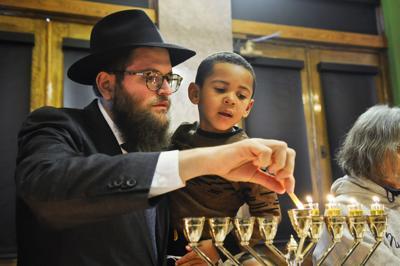 Rabbi Chaim Bruk and his son Menny Bruk light a menorah