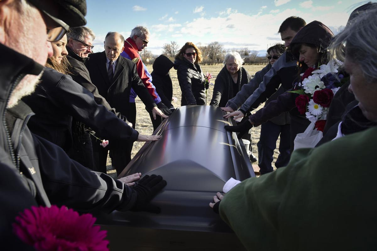 Those in attendance rest their hands on the casket of Laura Cook on Nov. 29