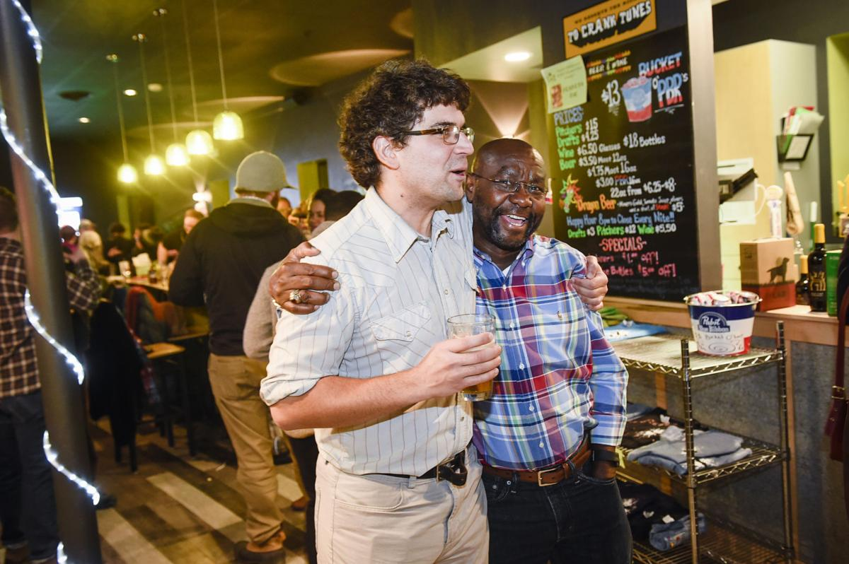 Wilmot Collins, right, and Andres Halladay, left, rejoice after election results were announced Tuesday night.