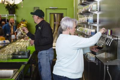 Owner Barbie Edwards, right, and Steve Edwards serve beers Friday afternoon at Snow Hop Brewery.