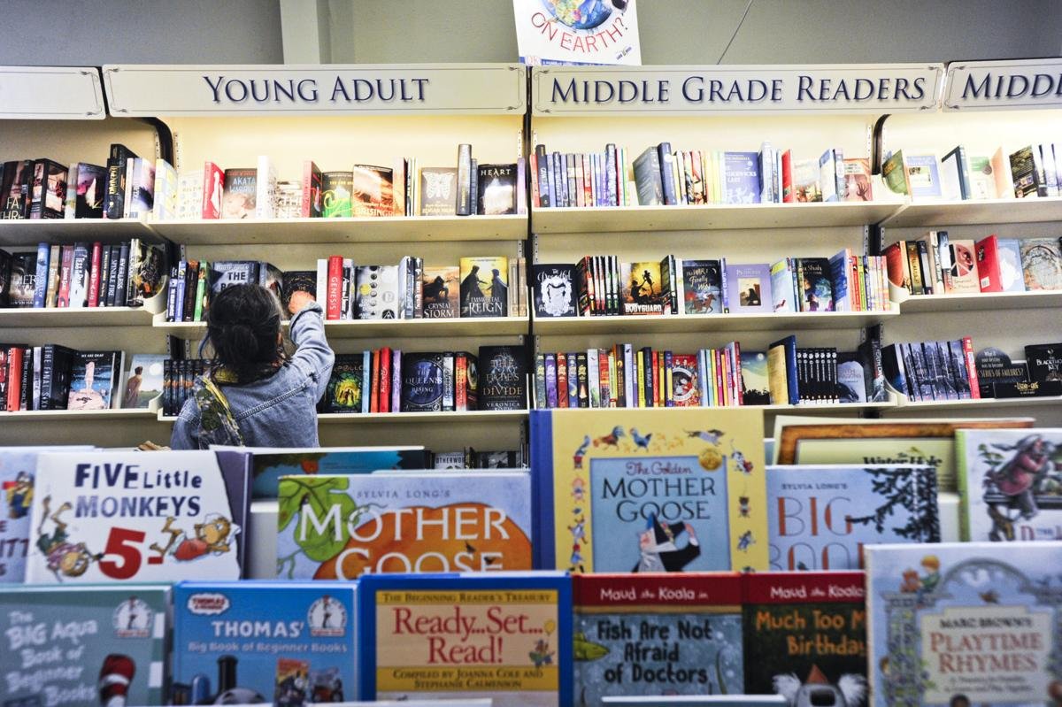 A woman browses the young adult section of Montana Book and Toy Company