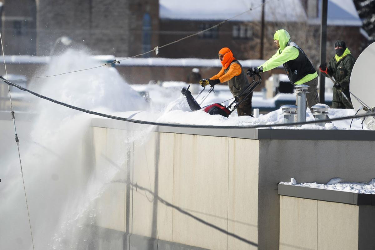 A team of snowblowers work to clear snow off the roof of the downtown post office