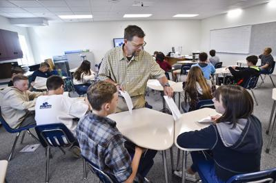 Science teacher Thomas Shive hands out materials to his ninth grade students