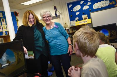 Librarian Marla Unruh, center, is surprised by Helena Education Foundation executive director Lisa Cordingley, left,