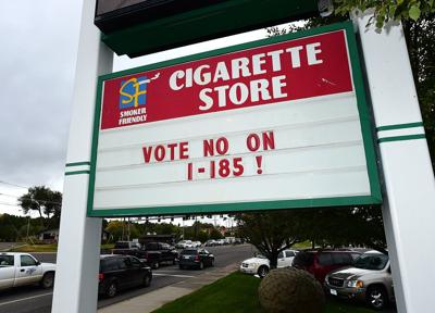 A sign in front of the Cigarette Store at Main Street and Airport Road in Billings Heights encourages voters to vote against I-185, which would add a ...