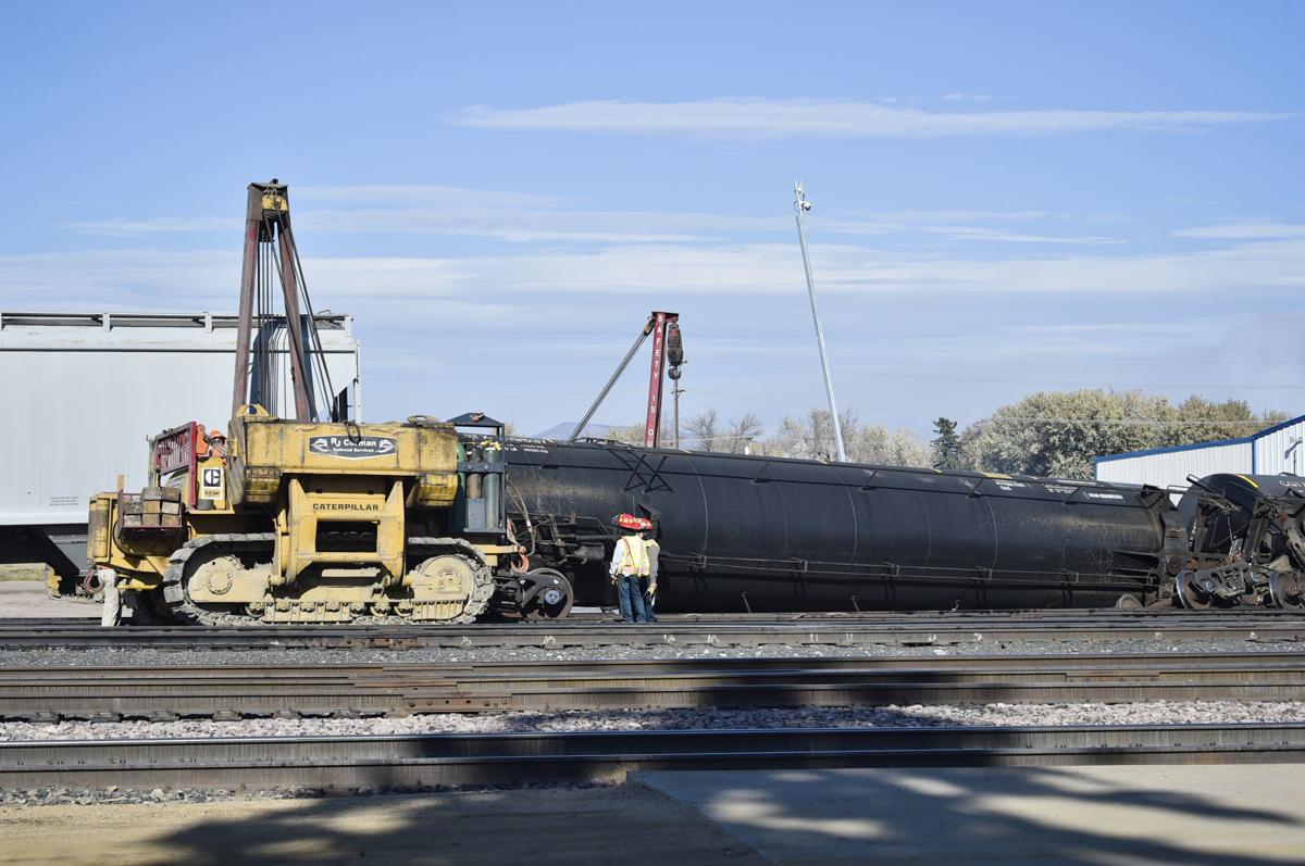 Montana Rail Link workers work to re-rail several train cars