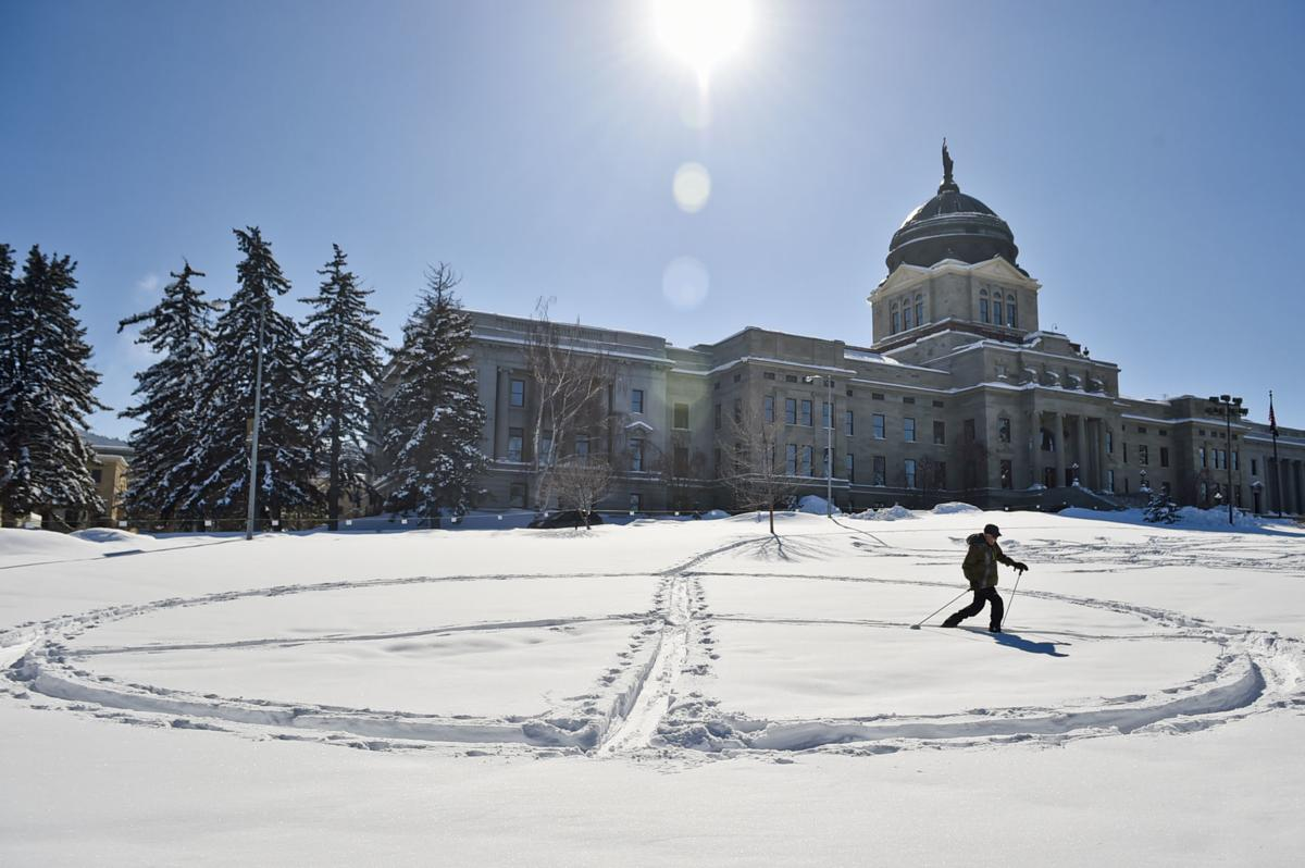Ron Casey skis a peace sign into the lawn of the State Capitol