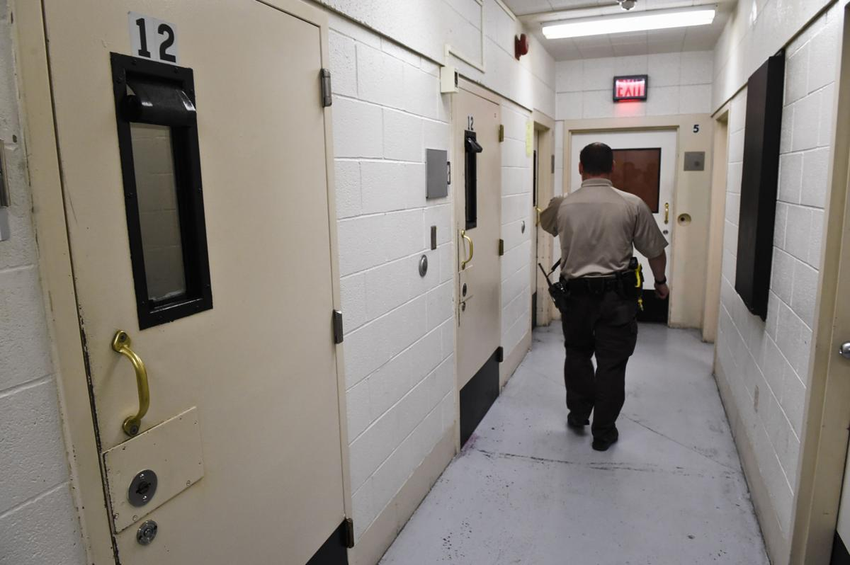A detention officer walks past holding cells near the booking area of the Lewis and Clark County Detention Center.