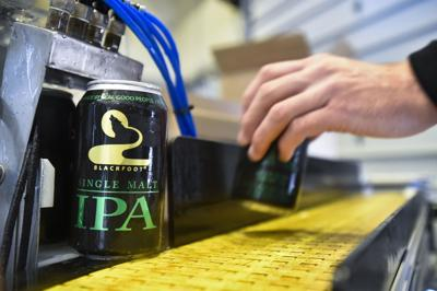 Cans of Blackfoot River Brewing Co. Single Malt IPA come off a mobile canning system