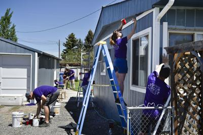 A team of volunteers works to spruce up Elmer Osborne's house