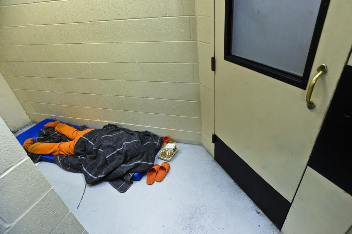 An inmate sleeps in a hallway outside an attorney meeting room in the Lewis and Clark County Detention Center