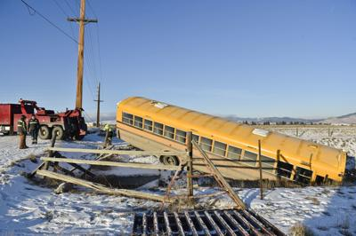 A wrecking crew works to pull a school bus out of the irrigation ditch