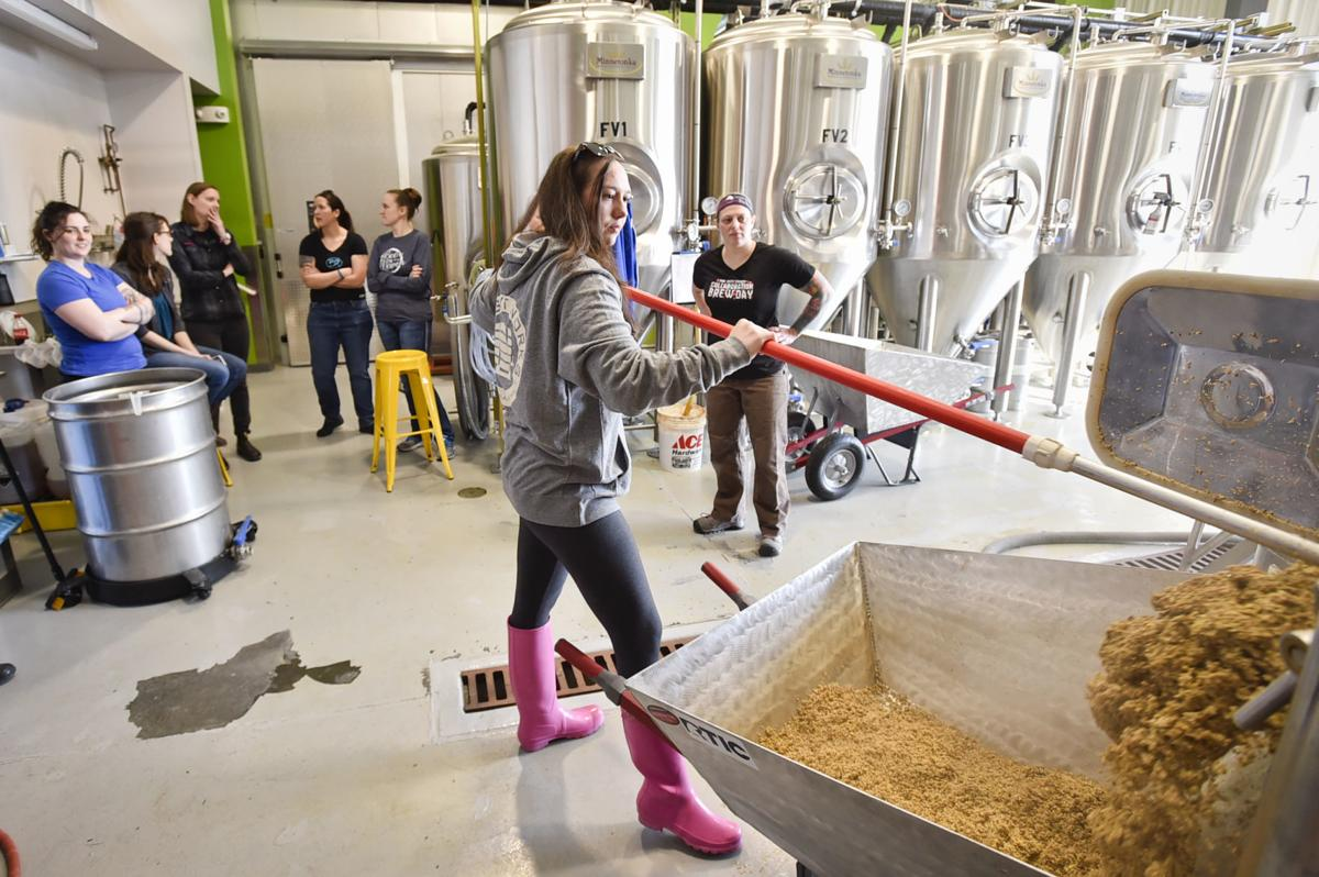 Kori Christianson scrapes grain out of a kettle Thursday during the Pink Boots Society