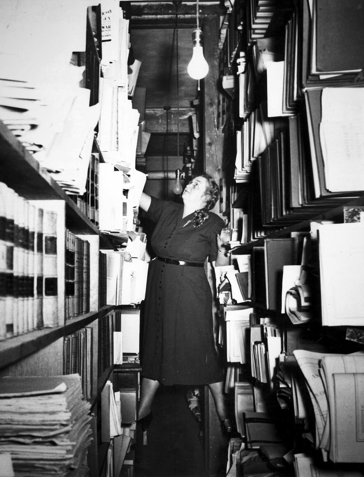 Librarian Hannah Wendel reaches for the top shelf