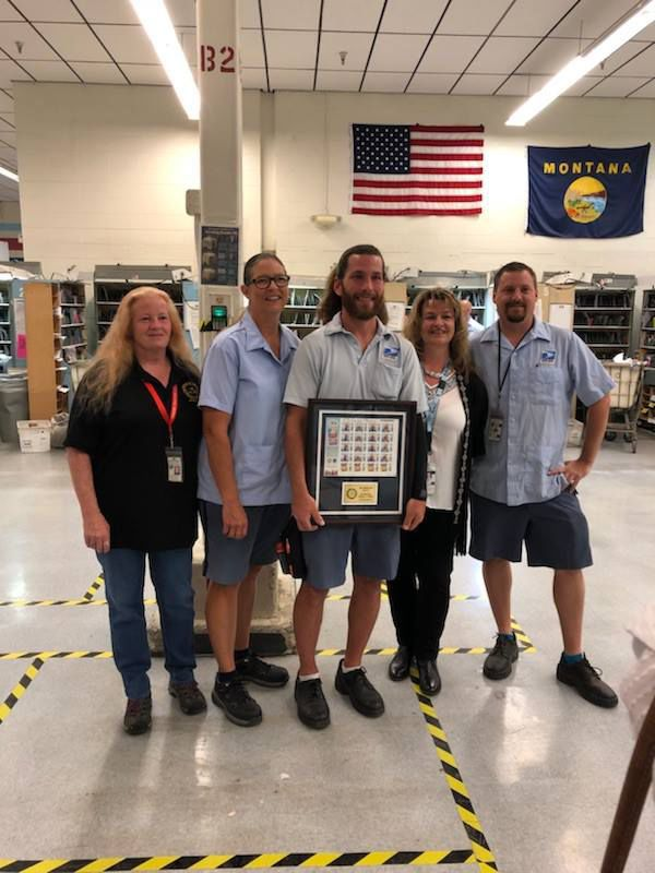 Helena Postal carriers hold an awarded plaque