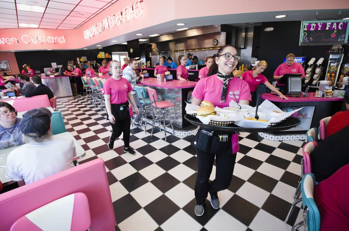A server hustles a tray of burgers