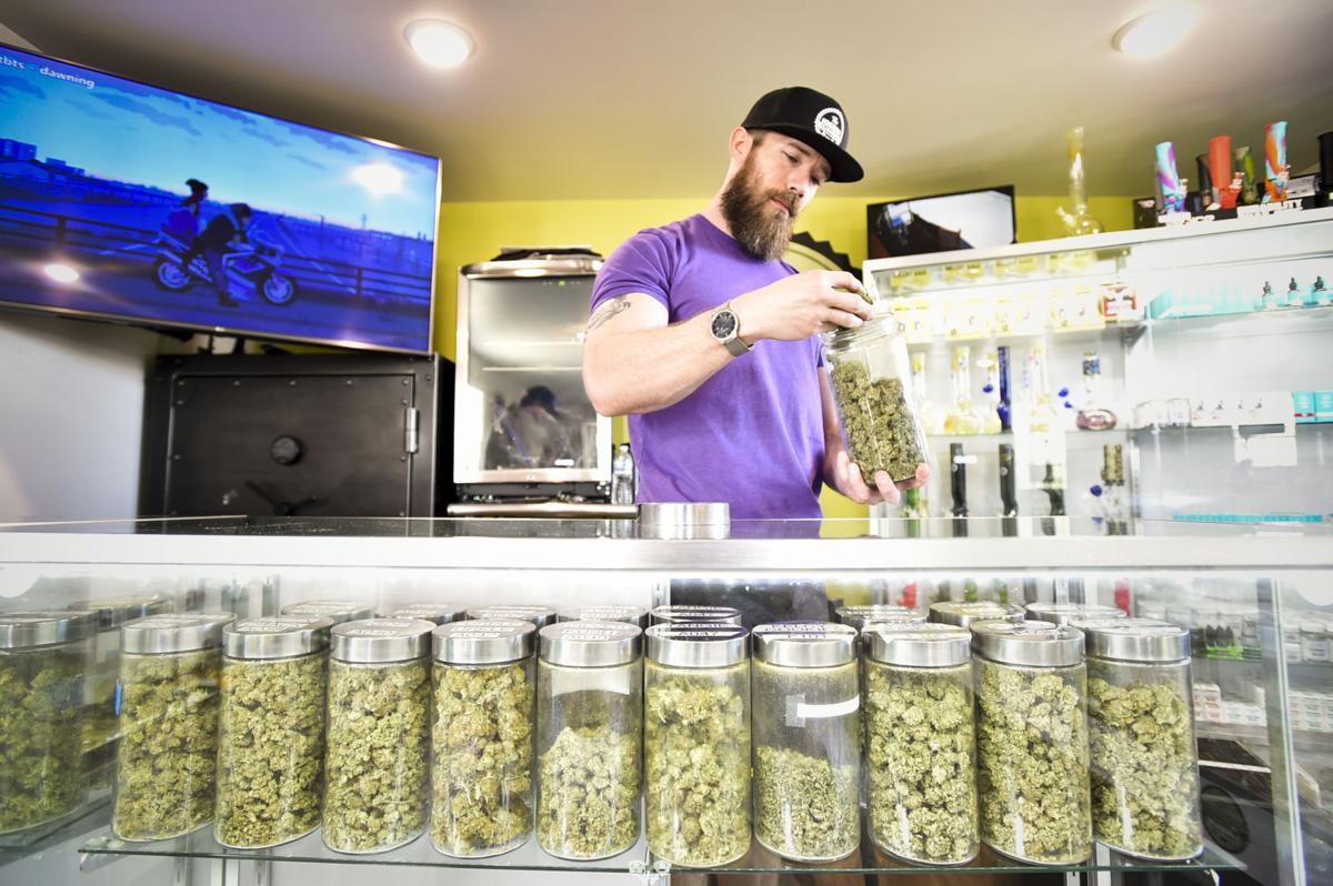 Josh Hughes rifles through a jar of medical marijuana