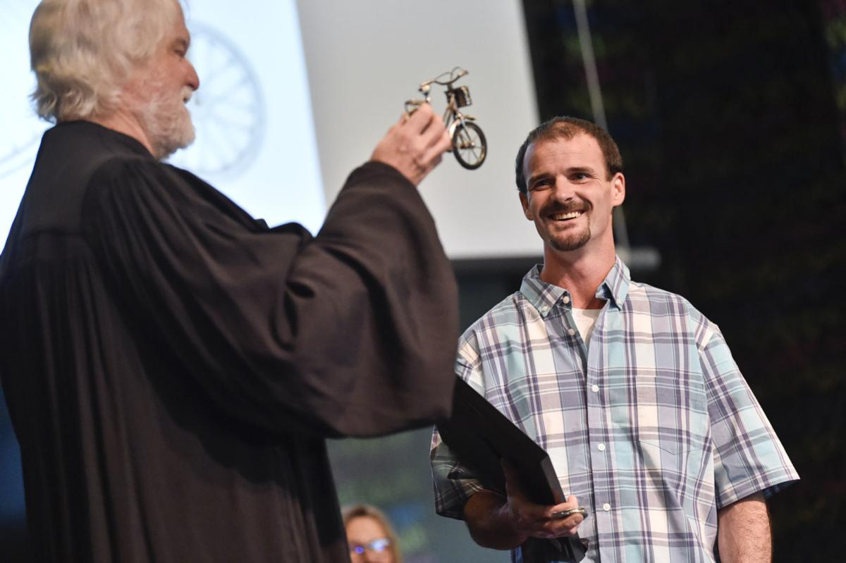 Sam Goulet receives his diploma and miniature bicycle during Monday's treatment court graduation