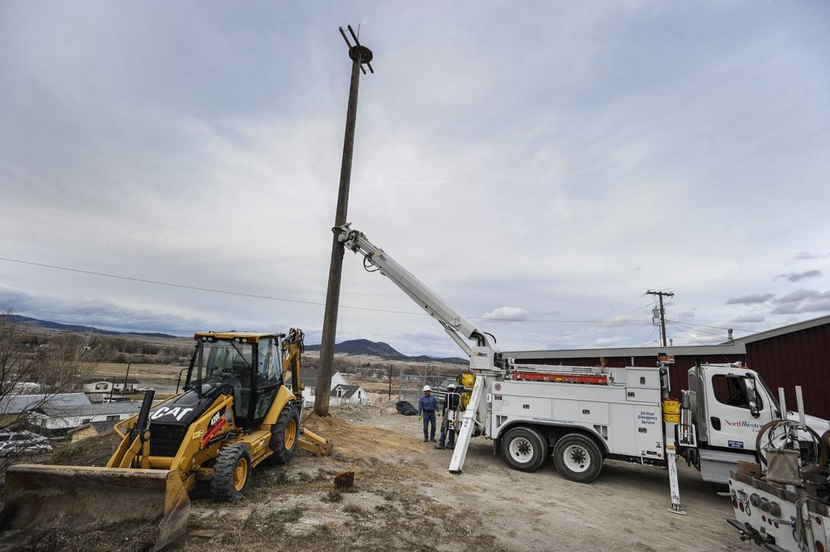 Northwestern Energy linemen install a pole and platform