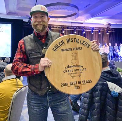 Tyrrell Hibbard, a co-owner of Gulch Distillers, hold up a best in class trophy