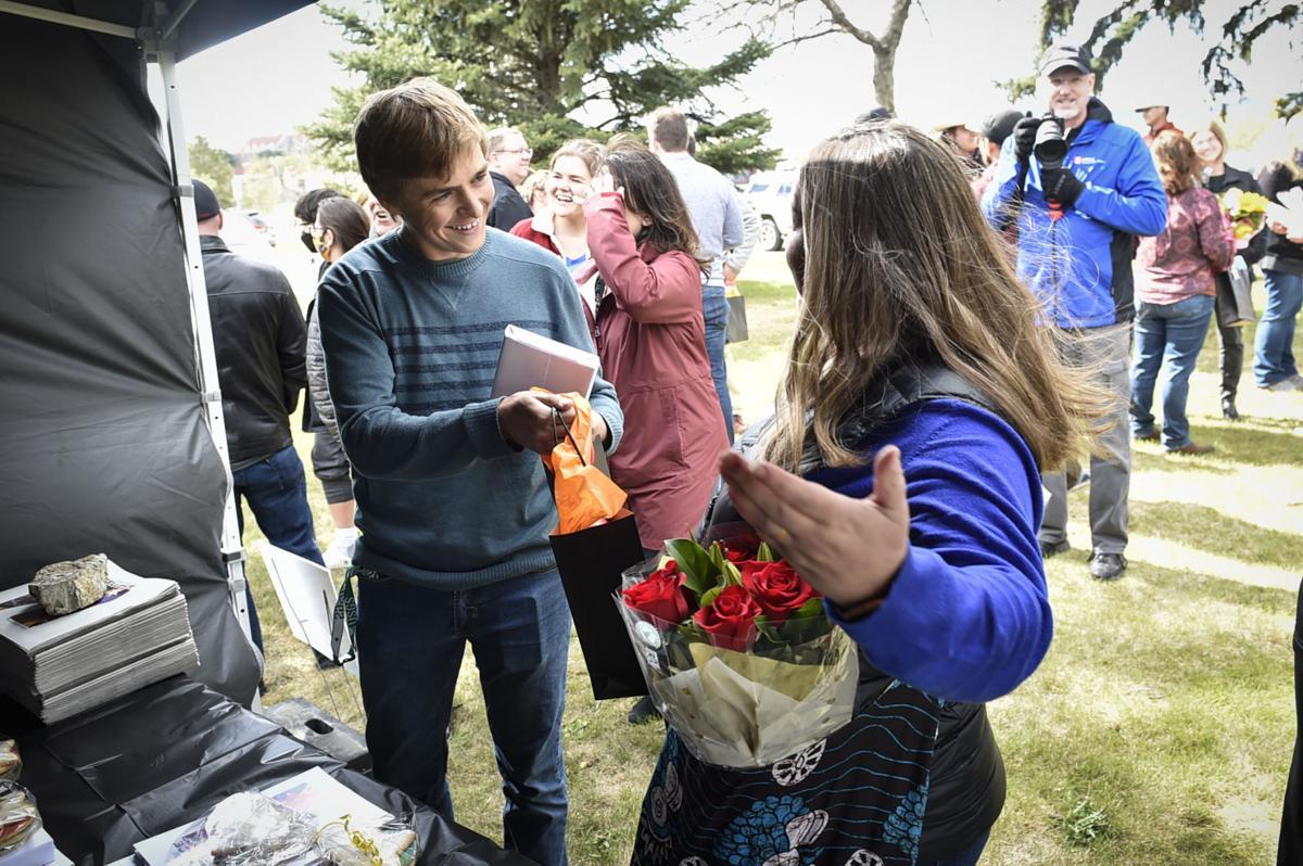 Helena High School student Heath Caldwell hands his teacher, Claire Pichette,