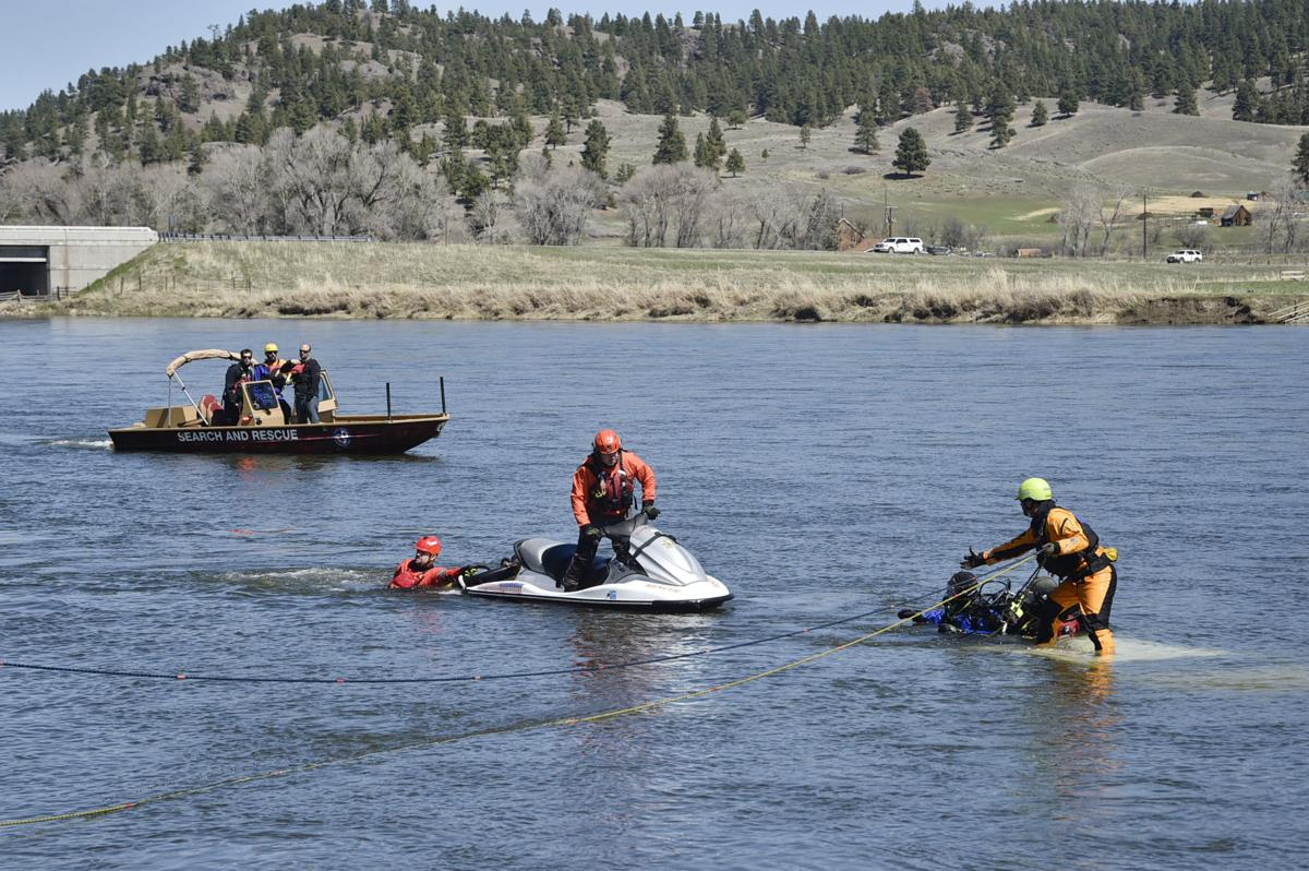 Search and rescue divers work to hook the submerged truck