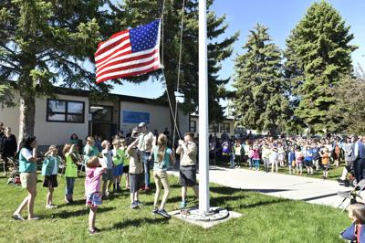 Group of Girl Scout and Boy Scouts lower the American Flag