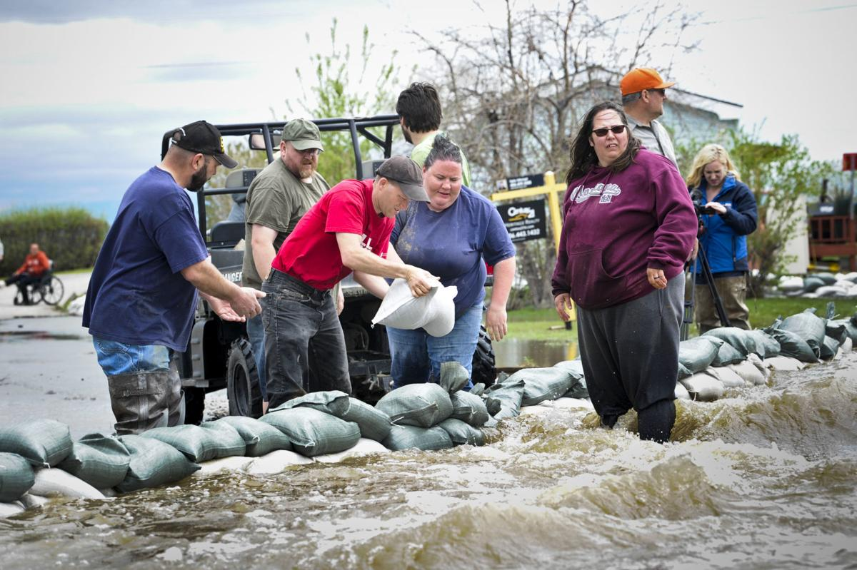 Residents and volunteers fight to divert flood waters in the Helena Campground and RV Park Monday.