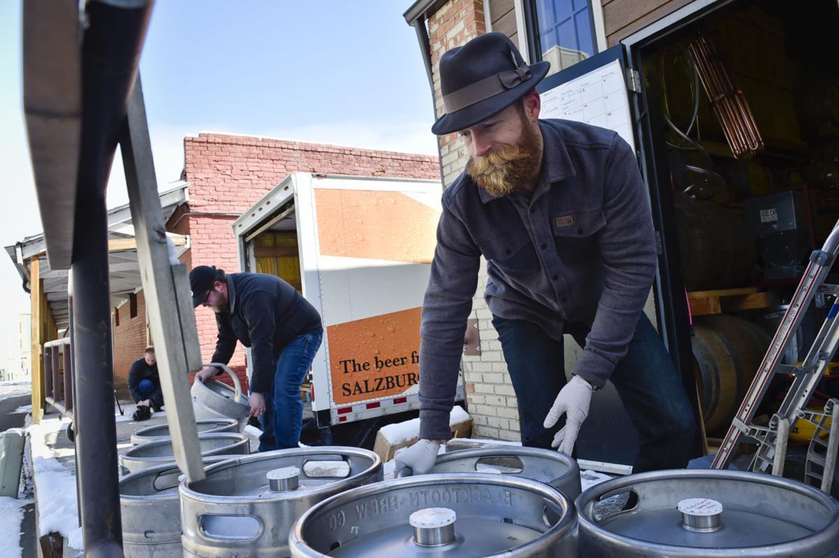 Gulch Distillers co-owner Tyrell Hibbard helps unload 30 unused kegs of beer