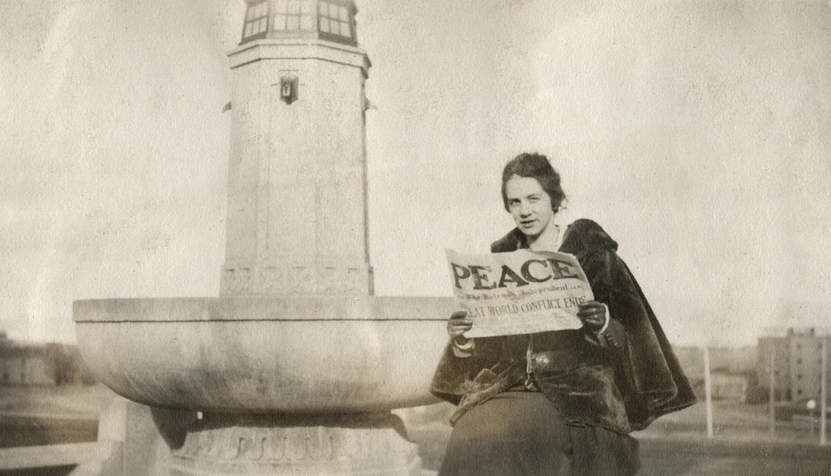"An unidentified woman seated on the Confederate Fountain in Helena holding up a newspaper with ""PEACE"" headline after the end of World War I."