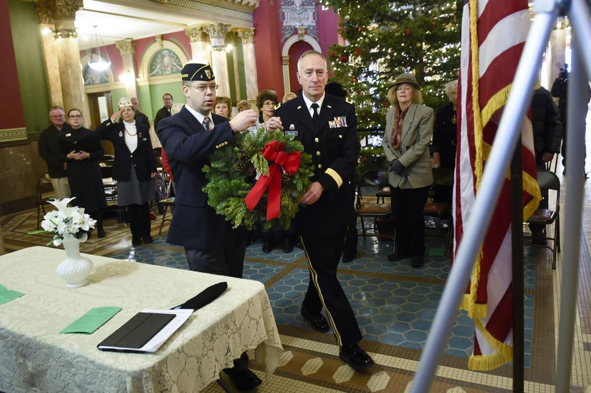 Maj. Joshua Clement, left, and Brig. Gen. Jeffrey Ireland, right, lay a wreath in the Capitol Rotunda Monday morning during the annual Wreaths Across America ceremony.