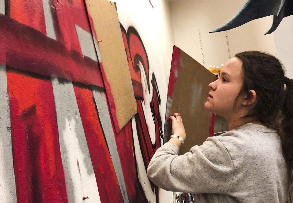 Delaney Day works on a mural recently along with other students from the Holter Museum's Afterschool Teen Arts Council.