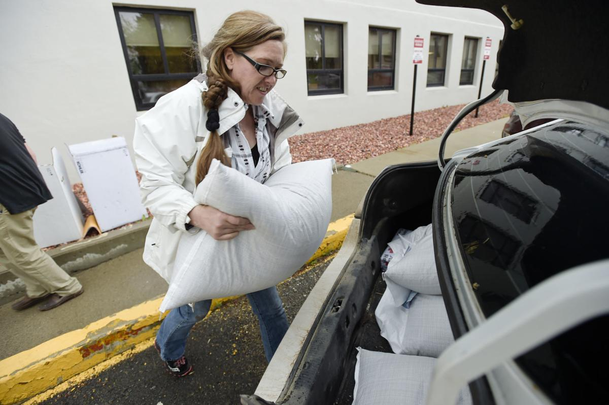 Kim Phillips loads a fifty-pound bag of industrial hemp seeds into her car