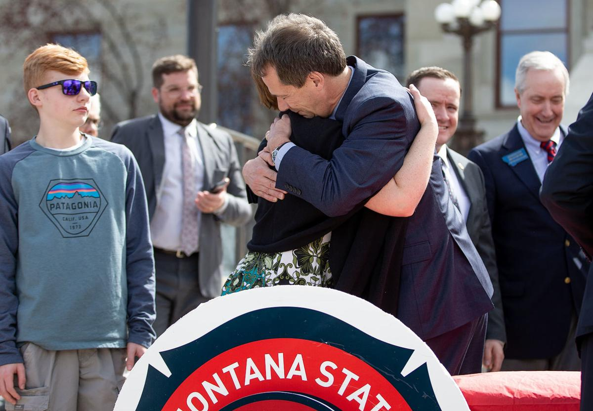 After the bill signing, Gov. Steve Bullock hugs Jill Baker,