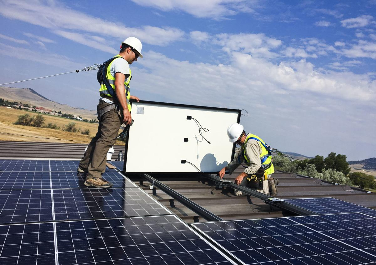 Crews members of Solar Montana install a solar panel array