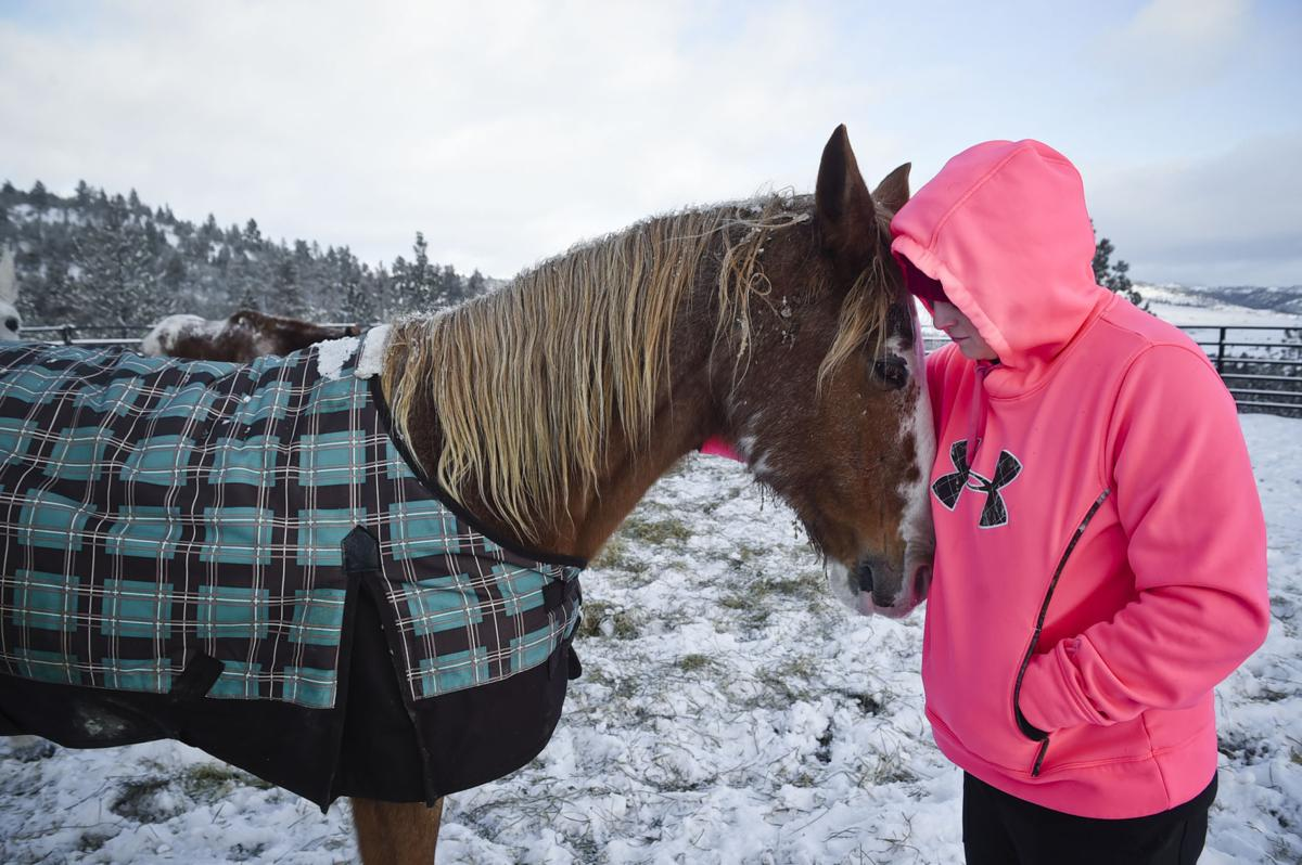Sherron Davis nuzzles one of the ten horses she recently rescued