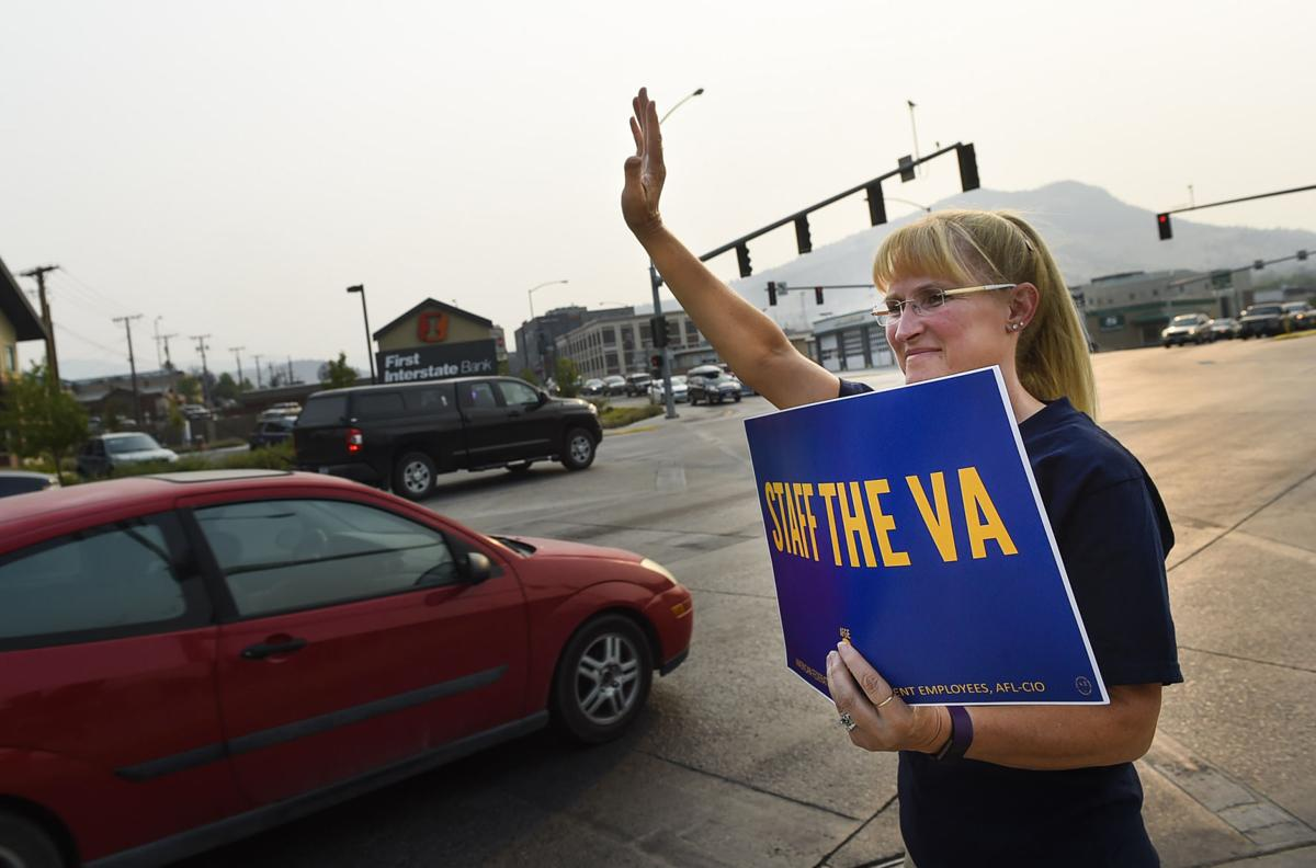 """Theresa Snyder holds a sign reading """"Staff the VA"""" Wednesday evening during a demonstration raising awareness about the 49,000 vacancies in the VA health care system."""