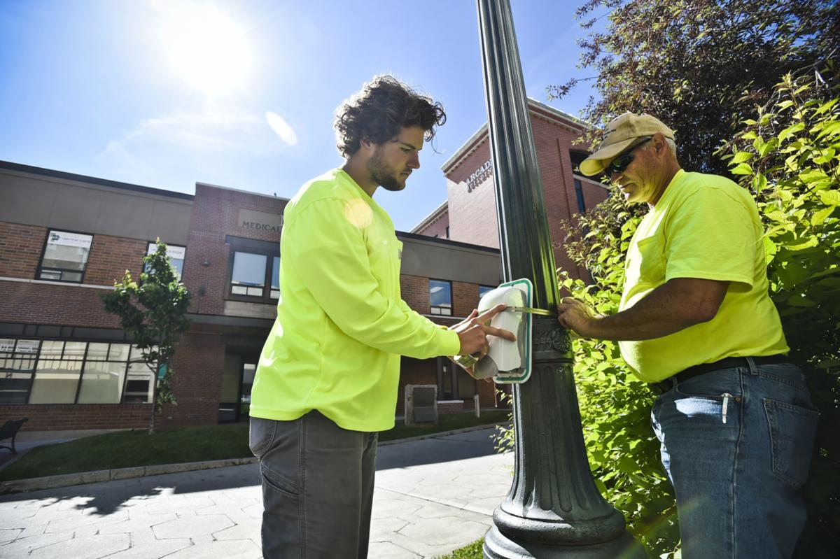 City of Helena workers install a hand sanitizer station on the Walking Mall on Monday morning.