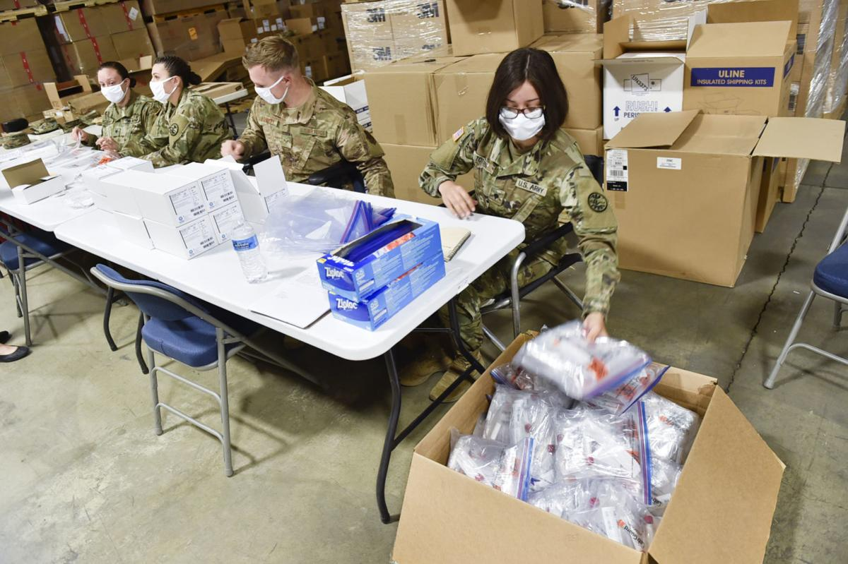 Soldiers from the Montana National Guard assemble COVID-19 testing kits - file