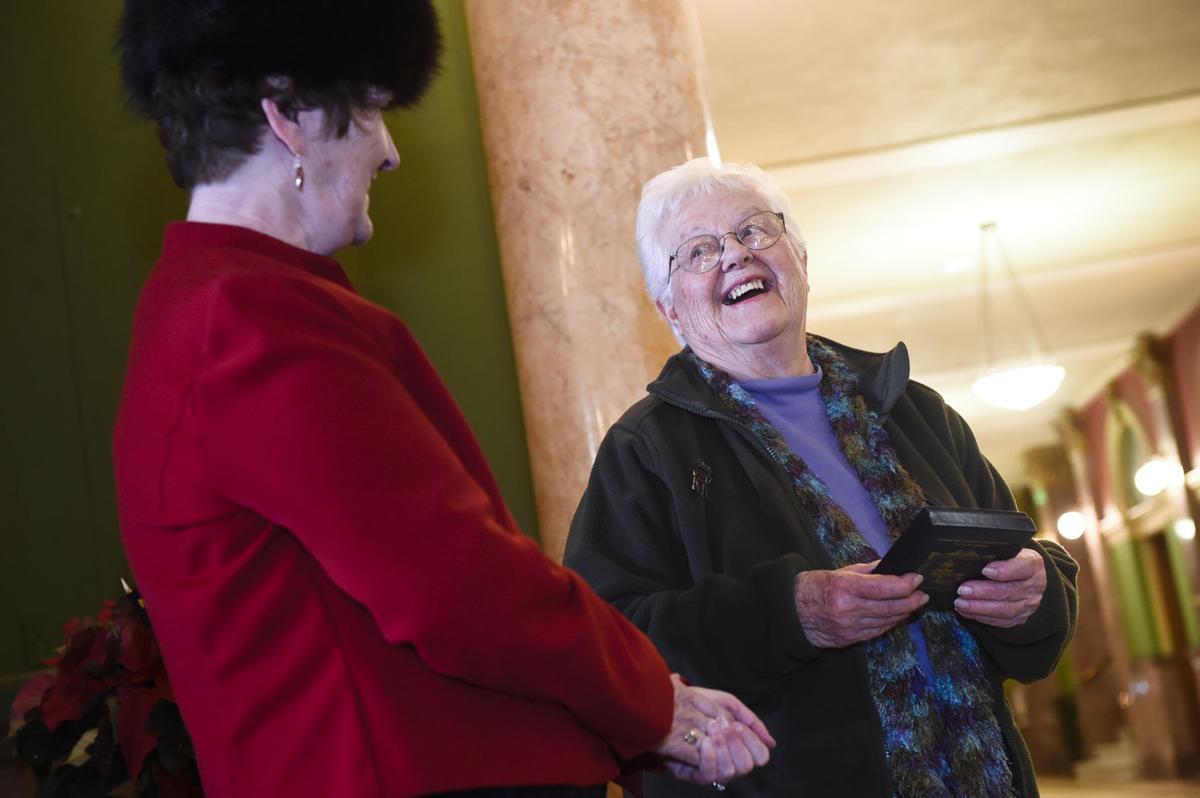 Gen Morgan, wife of Bob Morgan, right, laughs while receiving a Capitol Restoration Foundation ornament
