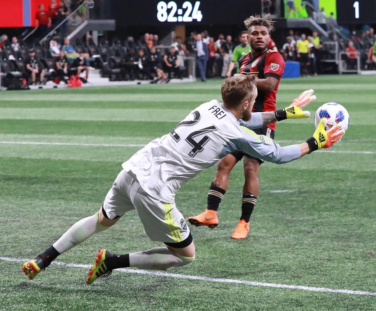 Seattle Sounders goalkeeper Stefan Frei blocks a shot as Atlanta United midfielder Josef Martinez looks on during the second half on Sunday, July 15, 2018, in Atlanta, Ga.